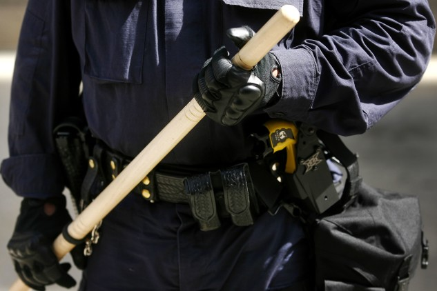 A police officer holds a nightstick.