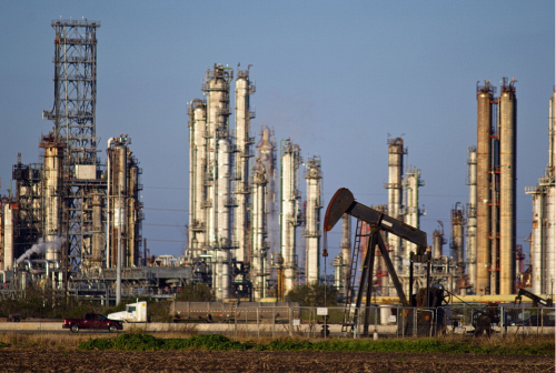 A refinery stands in the background as a pump jack operates in an oil field near Corpus Christi, Texas. In January crude oil prices fell to the lowest in 13 years.